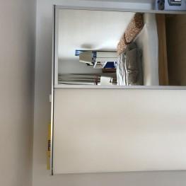 Weißer Schwebetürenschrank mit großem Spiegel